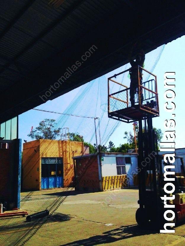Instalación de Malla anti-pájaros y antipalomas GUACAMALLAS® para proteger de aves problemáticas estructuras metálicas de fábrica con ayuda de grúa