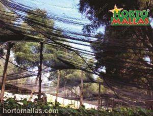 Malha/Rede de sombra OBAMALLA® colocada em postes de madeira.