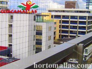 red anti pájaros en balcon con vista a la ciudad